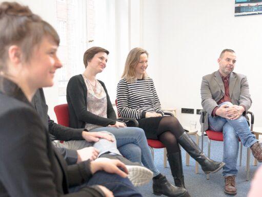 vier Personen sitzen auf Stühlen und schauen auf etwas