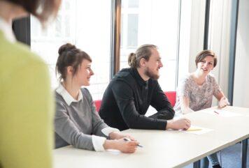 Personen sitzen nebeneinander an einem Tisch, die Gruppenleiterin steht links im Bild